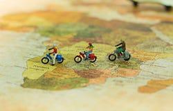 Miniaturowi ludzie, podróżnicy z bicyklem na światowej mapie, cyling miejsce przeznaczenia Zdjęcie Stock