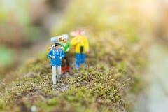 Miniaturowi ludzie: podróżnika odprowadzenie na drogach cluttered z trawą Używać podróżować miejsca przeznaczenia Zdjęcia Royalty Free