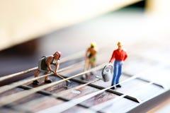 Miniaturowi ludzie: pracownik drużyna z gitarą akustyczną, czas real obraz stock