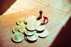 Miniaturowi ludzie, pracownik pracuje na stert monetach Zdjęcie Royalty Free