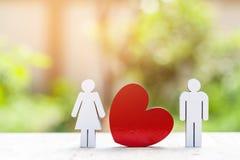 Miniaturowi ludzie rodziny i czerwieni serce na drewnianym tle Obraz Royalty Free
