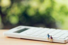 Miniaturowi ludzie siedzi na białym kalkulatorze używać jako tła biznesowy pojęcie i pracy zespołowej pojęcie z kopia bielem i pr zdjęcia stock