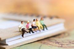 Miniaturowi ludzie siedzi na książce używać jako tła educati Fotografia Royalty Free