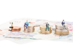 Miniaturowi ludzie siedzi na monety zakończeniu Fotografia Royalty Free