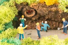 Miniaturowi pracownicy rozjaśnia drogę przemian po burzy Zdjęcia Stock