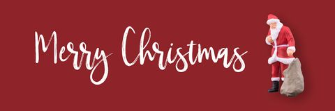 Miniaturowy Święty Mikołaj i prezenty zdojesteśmy z Wesoło bożych narodzeń tekstem z kopii przestrzenią zdjęcie royalty free