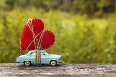 Miniaturowy błękit zabawki samochód niesie serce na rozmytym naturalnym gr Zdjęcie Royalty Free
