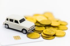Miniaturowy biały samochód umieszcza na stosie złociste monety Obrazy Stock
