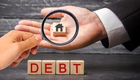Miniaturowy drewniany dom i «dług «wpisowy Nieruchomość, domowi oszczędzania, pożyczki wprowadzać na rynek pojęcie Zapłata nieruc zdjęcia royalty free