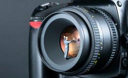 Miniaturowy mężczyzna cleaning kamery obiektyw Obraz Royalty Free