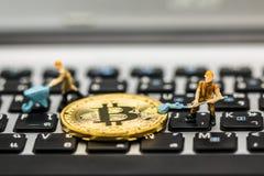 Miniaturowy mężczyzna kopie Minujący Złotych bitcoins obraz stock