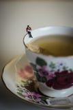 Miniaturowy postaci czytanie na stronie Herbaciana filiżanka Zdjęcie Royalty Free