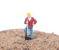 Miniaturowy pracownik z łopatą Zdjęcia Royalty Free