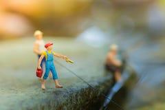 Miniaturowy rybaka obsiadanie na kamieniu, połów w rzece Makro- widok fotografia, use jako połów kariery pojęcie Zdjęcia Stock