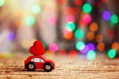 Miniaturowy samochód niesie Czerwonego serce na dachu Wakacyjna pojęcie miłość Zdjęcia Royalty Free