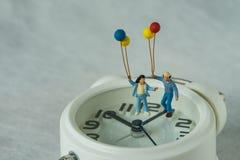 Miniaturowy szczęśliwy rodzinny mienie szybko się zwiększać pozycję na bielu alarmie Zdjęcia Stock