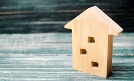 Miniaturowy trzypiętrowy drewniany dom na błękitnym tle minimalista Hipoteka, kredyt mieszkań nieruchomości domów prawdziwego czy zdjęcie royalty free