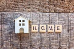 Miniaturowy zabawka modela dom z inskrypcja domu listów słowem na drewnianym tle zdjęcia royalty free