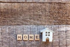 Miniaturowy zabawka modela dom z inskrypcja domu listów słowem na drewnianym tle zdjęcia stock