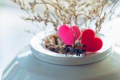 Miniaturpaare, die zusammen vor reizendem Blumenhintergrund mit rotem Herzen sitzen stockbilder