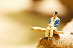 Miniaturplastikzahl Modellspielzeug des alten Mannes sitzen auf dem Stuhl Lizenzfreie Stockfotos