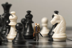 Miniaturpuppe und Schach Alter Reisender im Schachbrett Stockbild