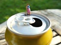 Miniaturputzfrau, die auf Besenstiel auf Getränkedose sich lehnt Lizenzfreie Stockbilder