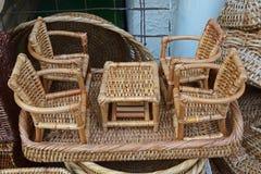 Miniaturrattan-Satz einzelner Couchtisch und vier bequeme Stühle Stockfoto