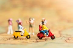 Miniaturreisende mit zwei Motorrädern Fahren Sie durch die Front von Wanderern auf Weltkarte mit als Reiseveranstalterkonzept Stockbild