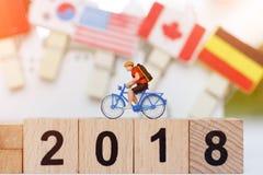 Miniaturreisender mit Fahrrad auf dem hölzernen Block mit Nr. 2018 Lizenzfreie Stockfotos