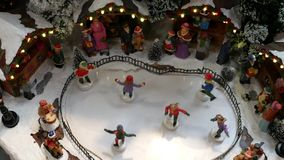 Miniaturrochenzahlen auf einer gefrorenen Eisbahn und im Hintergrund ist der Weihnachtsmarkt stock video footage