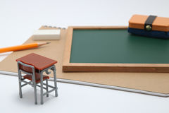 Miniaturschulbank, Tafel und Notizbuch auf weißem Hintergrund Stockfotografie