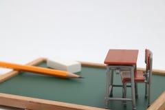 Miniaturschulbank, Tafel und Notizbuch auf weißem Hintergrund Stockbild
