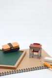 Miniaturschulbank, Tafel und Notizbuch auf weißem Hintergrund Lizenzfreies Stockbild