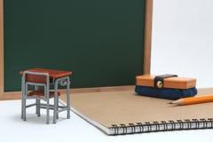 Miniaturschulbank, Tafel und Notizbuch auf weißem Hintergrund Stockfoto