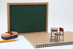 Miniaturschulbank, Tafel und Notizbuch auf weißem Hintergrund Lizenzfreie Stockbilder