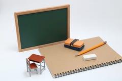 Miniaturschulbank, Tafel und Notizbuch auf weißem Hintergrund Lizenzfreie Stockfotos