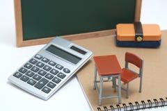Miniaturschulbank, Tafel und Taschenrechner auf weißem Hintergrund Stockbild
