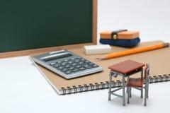 Miniaturschulbank, Tafel und Taschenrechner auf weißem Hintergrund Lizenzfreie Stockfotos