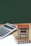 Miniaturschulbank, Tafel und Taschenrechner auf weißem Hintergrund Lizenzfreie Stockfotografie