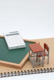 Miniaturschulbank, Tafel und Taschenrechner auf weißem Hintergrund Stockbilder