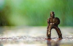 Miniaturspielzeugritter unter Regen mit grünem Hintergrund Stockbilder