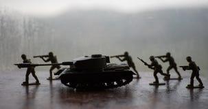 Miniaturspielzeugsoldaten und -behälter an Bord Schließen Sie herauf Bild des Spielzeugmilitärs im Krieg Lizenzfreies Stockbild