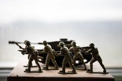 Miniaturspielzeugsoldaten und -behälter an Bord Schließen Sie herauf Bild des Spielzeugmilitärs im Krieg Lizenzfreie Stockfotografie