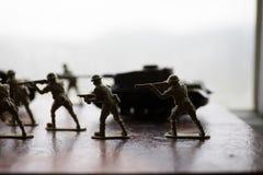 Miniaturspielzeugsoldaten und -behälter an Bord Schließen Sie herauf Bild des Spielzeugmilitärs im Krieg Lizenzfreie Stockbilder