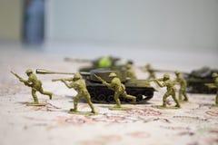 Miniaturspielzeugsoldaten und -behälter an Bord Schließen Sie herauf Bild des Spielzeugmilitärs im Krieg Lizenzfreie Stockfotos
