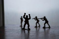 Miniaturspielzeugsoldaten und -behälter an Bord Schließen Sie herauf Bild des Spielzeugmilitärs im Krieg Stockbild