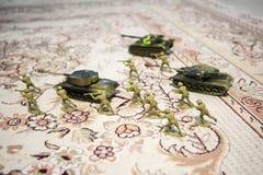 Miniaturspielzeugsoldaten und -behälter an Bord Schließen Sie herauf Bild des Spielzeugmilitärs im Krieg lizenzfreies stockfoto