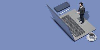 Miniaturunternehmensleiter, der mit einem Laptop arbeitet lizenzfreie stockfotografie