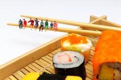 Miniaturvölker mit Sushi Stockfoto